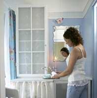 Et gammelt vindu som lå og støvet ned på loftet fikk nytt liv som skapsdør på badet. Yndige blonder ble festet på vinduets bakside med stiftepistol.