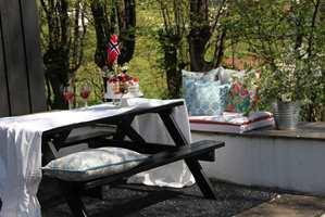 Med et lunende teppe under bordet, noen flotte puter og tekstiler er det dekket til fest. En enkel rengjøring av både møbler og terrasse gjorde uteplassen innbydende.