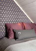 Det auberginefargete tapetet med gull gir liv til den asymmetriske, korte veggen og skaper en sofistikert huleeffekt; et bevis på at små rom kler mørke farger.