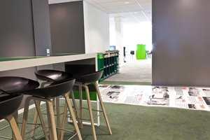 Det grå gulvet brytes opp av grønt ved sentrale plasser. Nedfelte glassplater med trykk forteller avisens og byens historie i en lang korridor midt i lokalet.