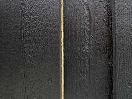 For å unngå synlige tørkesprekker er det best å påføre maling før kledningen spikres opp på fasaden.