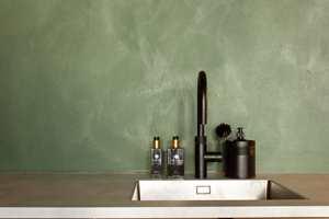INDUSTRIELL VEGG: Kjøkkenveggen er påført KC14, i fargen «Dark Emerald» fra Detale CPH. Dette er en sparkelmaling som løfter det industrielle preget i leiligheten, samtidig som det gir et lunt uttrykkk. Under sparkelen er veggen grunnet med Interior High Finish 5, i en farge som er plukket ut for å stemme overens med fargekoden på sparkelen.