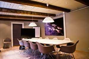 Møterommet er malt med en mørkere veggfarge enn ellers i kontoret. Himlingen er et nytt paneltak med innfelte spotlights og synlige takbjelker.