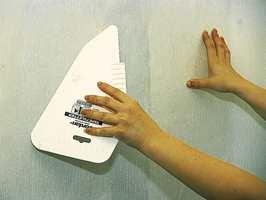 Bruk en tapetglatter med runde hjørner og stryk tapetet på plass.