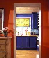 Her har både gangen og kjøkkenet fått sterke primærfarger i slekt med våre opprinnelige bondefarger. Rent rødt sto mot rent blått (5040-R80B),  frisket opp av liftgardiner i solfarge. Taket var fortsatt umalt tre, men nå med downlights.