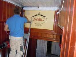 Det gamle skiltet over trappen er bevart. Panelet rundt ble malt.