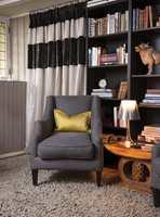 SKJULT GARDEROBE I motsatt ende av soverommet skjuler en fotsid gardin en nisje med et walk-in closet. Rolige, mørkladne farger i selskap med en gammel, gyllen, afrikansk krakk, som fungerer som bord og tilfører en varm farge.