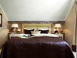 Stor effekt – hvitt tak, tapeter og sengegavl skaper en hyggelig atmosfære i et stilig rom.