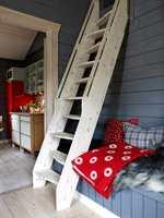 Trappen opp til hemsen har samme farge som gulvet, og stikker seg derfor ikke ut, men bidrar til å skape helhet.  I bakgrunnen skimtes kjøkkenet.