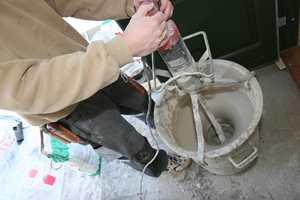 Store bøtter og maskinelt blandeutstyr er nødvendig for å få glatt nok avrettingsmasse. Dette er ikke håndarbeid. Som regel går det med store mengder masse og vann.