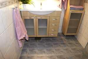 Nytt bad med avstemte keramiske fliser på gulv og vegg og et nytt baderomsmøblement.