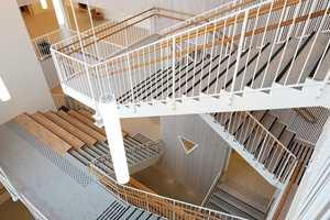 <b>KOMFORTABELT TRE:</b> I trapperommet er det foruten betongvegger også trespiler som skal bidra til økt komfort. Treet som er et hygroskopisk materiale virker positivt på luftfuktigheten, men det har også en funksjon for akustikken. Bak trespilene er det nemlig montert en absorbenter som skal bidra til et levelig lydbilde i det store fellesarealet.