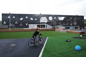 <b>UTVENDIG:</b> Mot sør har skolen en spennende fasade. Overflatematerialet skulle være vedlikeholdsfritt, et krav som ble løst med blankpolert betong med larvikitt-innslag.
