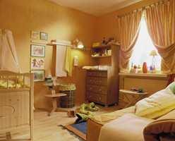 Et lunt babyrom med mye plass og varme farger.