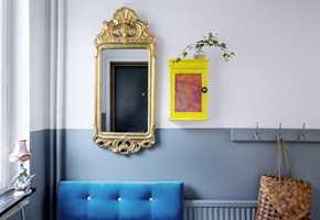 <b>SPENNING I DETALJENE:</b> Tofarget vegg gir en fin effekt, uten å virke rotete. Sofaen i kraftig turkis og speilet i gull er viktige stemningsskapere, og nøkkelskapets småfrekke gulfarge er en spennende kontrast til de øvrige fargene. Radiatoren er godt kamuflert i samme farge som veggen. (Foto: Beckers)
