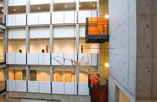 Et atrium med gjennomgående betongflater - behandlet med fargeløs malingbase. Alle de hvite akustikkplatene er sparklet, fuget og malt hvite med Nordsjö Bindoplast 7.