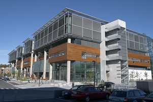 BIs nye campus. Auditorier og klasserom, dels med oljebehandlet lerk fra Norwood, stikker ut fra glassfasadene. Langs bygget er det små forhager.