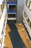 Spennende vekslinger mellom materialer og farger. Her er sort vinyl i samspill med høykant-parkett, mens gangbroene leder inn til blå sektor.