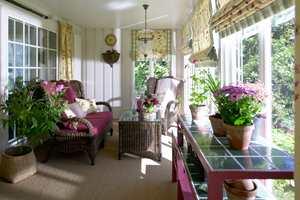 <b>LUN HYGGE:</b> Terrassen ble glasset inn, og forandret til et solrikt rom. Kurvmøbler, fargerike tekstiler, frodige planter og gulvteppe av sisal – atmosfæren er god!