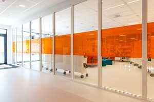Skolen har mange innvendige vinduer og glassvegger. For å tilføre interiørene mer karakter er det i stor grad benyttet transparent, farget film som matcher de stedvise temafargene, som her i skolens bibliotek.