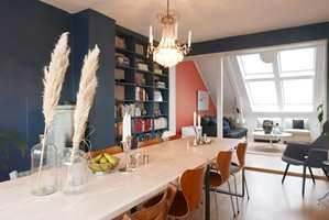 <b>HYGGELIG ATMOSFÆRE:</b> Borte er det kalde. De malte veggene i spisestuen er blå (S 6020-R90B), og gir rommet et rolig, lunt uttrykk, samtidig som de løfter frem de andre fargene mer enn hvitt. Farger kan brukes til å skape soner, og en oransje vegg (S 2050-Y70R) avgrenser stuedelen, som etter hvert vil få samme farge på alle veggene. Platen på spisebordet er behandlet med hvit gulvolje og gulvlakk, mens understellet er laget på mål hos en smed.