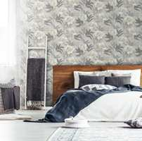<b>MASKULINT:</b> Den brunbeisede sengegavlen og innslag av mørk grått og blått gir rommet et rustikt og maskulint preg. Tapetet er fra Borge, kolleksjon Kalkmix.
