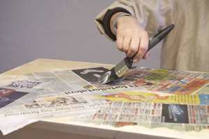 Påfør nok et lag tapetlim oppå papirstykkene. Begynn på midten og jobb deg ut mot kantene.