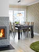 Et bladrikt, gyllent fibertapet i spisestuen understreker den naturinspirerte stilen, og det tar opp igjen fargen i gummigulvet på kjøkkenet. Det skaper også en pen helhet mellom rommene.