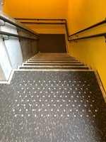 <b>LIKE TRAPPELØP:</b> Alle bi-trappene har gule vegger, og linoleum i mørkegrått med hvite spetter. Belegget er ikke lagt helt ut på avsats og trappetrinn, slik at betongen skaper en tøff ramme.