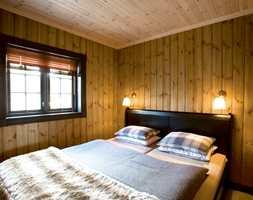 Soverom med lys panellakk i tak og interiørbeis på vegg. Vinduene i den grå farge, sengen er i sort og sengeutstyr i matchende blå- og bruntoner.