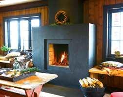 Den murte peis er selvdesignet av hytteeier og malt med interiørmaling i samme grå som vinduene - i en matt glansgrad 10.