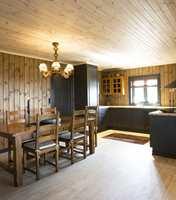 Overgang fra stue til spiseplass og kjøkken. Kjøkkeninteriøret er i samme gjennomførte grå som dør og vindu.