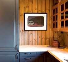 Kjøkkendetalj hvor skap til høyre, antikvarisk gjenstand og benkplate er ton-i-ton med interiørbeisen. Den grå farge går igjen på skapene.