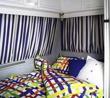 Sofabenk og bord forvandles med enkle grep til en dobbeltseng. Med fargerikt sengetøy blir det et riktig innbydende soverom.