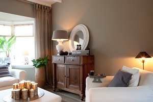 Sofa og lenestoler er lyse, og store vinduer sørger for godt med dagslys.