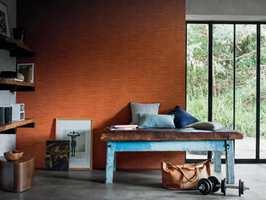 <b>TAPETKONTRAST:</b> Noen ruller med høstgyllent tapet skaper lunhet i rom med murvegger og betonggulv. En blåmalt rustikk benk med lærsete binder det varme og kalde, harde og myke fint sammen. Tapetet er fra Casamance/GreenApple. (Foto: Green Apple)