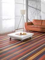 Den oransje fargen fra gulvet tas opp igjen i sofaen, ellers er rommet hvitt og nøytralt.