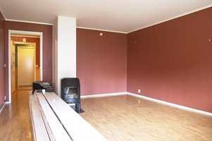 Stuen før. Bonderøde vegger og mørkt vinylgulv gjorde stuen mørk og kjedelig.