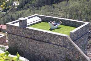 I dette italienske huset hentes dagslys fra en skrå glassflate på takets terrasse. Det gir en jevn daglysflate på innvendig stue.