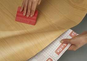 Stryk ut luftbobler, og jevn ut med en tapetglatter eller en klut.
