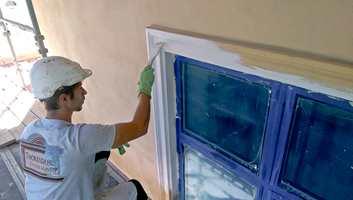 Når den gjennomfargede sluttpussen er påført, males gesimser og vindusomramminger for hånd.
