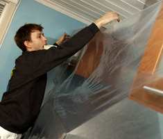 Dekk til gulv og møbler med plastfolie eller dekkpapir, og legg maskeringstape langs taklisten.