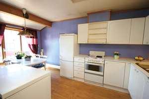 Kjøkkenet før: Den hvite, laminerte kjøkkeninnredningen var i fin stand, men så utdatert ut. For å få bedre plass til spisebord, ble kjøleskapet flyttet.