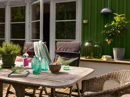 <b>NYT DAGENE:</b> Med en velholdt terrasse, gode tekstiler, grønne planter og en hyggelig sitteplass kommer du langt. Husveggen er malt i fargen Granbarr 091 fra Beckers.