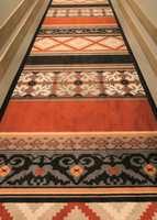 Teppebelagte korridorer hvor interiørarkitekt har valgt en modifisert variant av Ege-mønsteret Village Print.