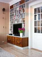 En kyndig snekker integrerte en skjenk i bokhyllen som skjuler ledninger og kabler fra TV og musikkanlegg.