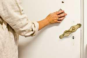 Skap god vedheft til ny maling ved å slipe lett over dørbladet med en finkornet slipekloss eller slipepapir.