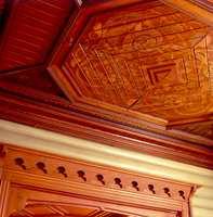 Taket inne på Holmenkollen Park hotell. Her er det ikke spart på noen ting, verken i måten treverket er lagt på eller den malte dekorasjonen. Tømmerveggene er malt gule og dørene har flotte omramminger i oljet tre.