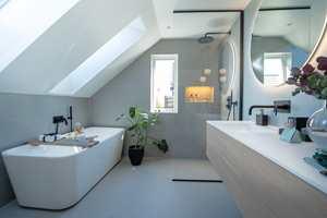 <b>SPA-FØLELSE:</b> Vegger og gulv er kledd med samme flis, en 90 x 90 centimeter stor flis med matt marmorert, lys grå overflate. Store fliser med få og smale fuger gir et rolig uttrykk. Alle rør er lagt inn i veggene, og dusjveggen er laget av kvalitetsglass. Sammen gjør dette at badet er lett å holde rent og pent, slik at du beholder den luksuriøse spa-opplevelsen på badet i mange år.