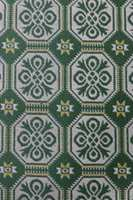 Et teppe med mønster i fine grønn- og gultoner.